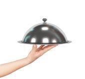 Ciérrese encima de la mano del camarero con la cubierta y la bandeja de la tapa de la campana de cristal del metal Imagenes de archivo