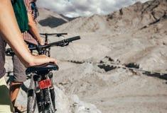Ciérrese encima de la mano del hombre de la imagen en la silla de montar de la bicicleta Dos motoristas del maountain Fotos de archivo libres de regalías