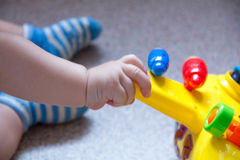Ciérrese encima de la mano del niño que juega el juguete Niño que se divierte y que lo construye fuera de ladrillos brillantes de fotos de archivo