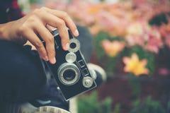 Ciérrese encima de la mano del ` s de la mujer con las flores del tiroteo del foco de la cámara del vintage Fotografía de archivo libre de regalías