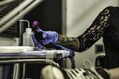 Ciérrese encima de la mano del tattooer con el guante del látex que sostiene una tinta del tatuaje nee imagenes de archivo