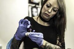 Ciérrese encima de la mano del tattooer con el guante del látex que sostiene una tinta del tatuaje nee fotografía de archivo
