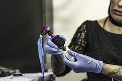 Ciérrese encima de la mano del tattooer con el guante del látex que sostiene una tinta del tatuaje nee imagen de archivo