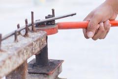 Ciérrese encima de la mano del trabajo con el doblador de barras de hierro viejo Foto de archivo libre de regalías