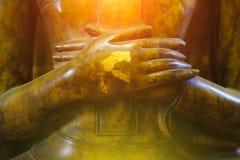 Ciérrese encima de la mano en la estatua de Buda con efecto luminoso Fotos de archivo libres de regalías
