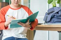 Ciérrese encima de la mano de la escritura masculina del adolescente con el lápiz en el cuaderno a Imagen de archivo
