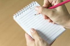 Ciérrese encima de la mano de la imagen que sostiene el lápiz y el cuaderno fotografía de archivo