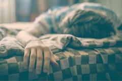 Ciérrese encima de la mano masculina enferma joven que miente en cama mientras que lucha con el ilness f foto de archivo libre de regalías