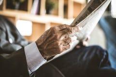 Ciérrese encima de la mano mayor del hombre de negocios de la imagen con los periódicos imágenes de archivo libres de regalías