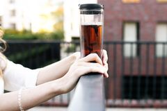 Ciérrese encima de la mano de la mujer en puesta del sol con la taza de té, copyspace fotos de archivo libres de regalías
