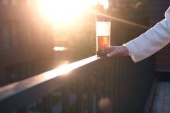 Ciérrese encima de la mano de la mujer en puesta del sol con la taza de té, copyspace imagen de archivo libre de regalías