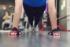 Ciérrese encima de la mano de la mujer que hace pectorales en el gimnasio Muchachas del entrenamiento en el pasillo Manos con gua Fotos de archivo