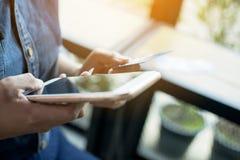 Ciérrese encima de la mano de la mujer que lleva la camisa azul de la mezclilla que lleva a cabo el pH móvil fotos de archivo