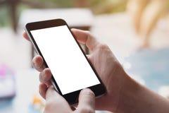 Ciérrese encima de la mano de la mujer usando un teléfono elegante en la cafetería del café foto de archivo