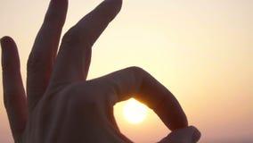 Ciérrese encima de la mano que muestra la AUTORIZACIÓN del símbolo de la muestra del gesto en la cámara lenta contra el cielo de  almacen de video