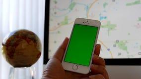 Ciérrese encima de la mano que sostiene iphone verde de la pantalla y que usa el mapa de Google almacen de metraje de vídeo
