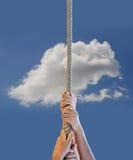Ciérrese encima de la mano que sostiene la cuerda y el cielo azul Foto de archivo
