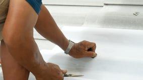 Ciérrese encima de la mano de un hombre que la llave del uso está girando el tornillo para fijar la teja de tejado almacen de video