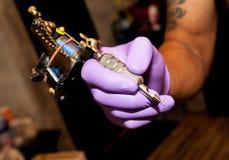 Ciérrese encima de la mano y de la máquina del tatuaje Imagenes de archivo