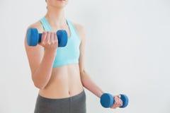 Ciérrese encima de la mediados de sección de la mujer con pesas de gimnasia Fotografía de archivo