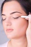 Ciérrese encima de la mirada de aplicar el lápiz cosmético Foto de archivo