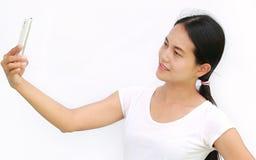 Ciérrese encima de la muchacha asiática que toma imágenes de sí misma a través del teléfono celular en el fondo blanco Foto de archivo