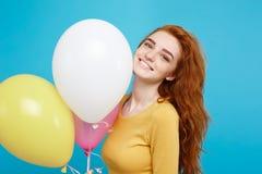 Ciérrese encima de la muchacha atractiva hermosa joven feliz del redhair del retrato que sonríe con el globo colorido del partido Foto de archivo libre de regalías
