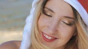 Ciérrese encima de la muchacha en el sombrero de santa que sonríe y que mira en cámara lentamente metrajes