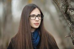Ciérrese encima de la muchacha hermosa en vidrios azules de una bufanda de la capa negra que camina en el otoño/la primavera Fore Fotografía de archivo libre de regalías
