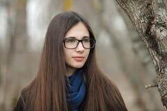 Ciérrese encima de la muchacha hermosa en vidrios azules de una bufanda de la capa negra que camina en el otoño/la primavera Fore Imagen de archivo libre de regalías