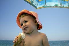 Ciérrese encima de la muchacha sonriente adorable del retrato que come el helado en la playa Foto de archivo libre de regalías