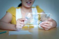 Ciérrese encima de la mujer asiática del tiro que usa claramente la tableta para el cybe futurista Imagen de archivo libre de regalías