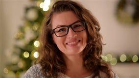 Ciérrese encima de la mujer joven feliz, lentes que llevan, mostrando sonrisa dentuda en la cámara contra fondo del árbol de navi metrajes