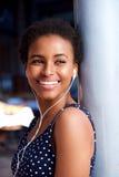 Ciérrese encima de la mujer joven sonriente que escucha la música con los auriculares imagen de archivo