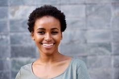Ciérrese encima de la mujer negra joven hermosa que ríe contra la pared gris foto de archivo libre de regalías