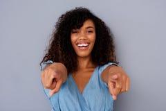 Ciérrese encima de la mujer negra joven hermosa que sonríe y que señala los fingeres imagen de archivo libre de regalías