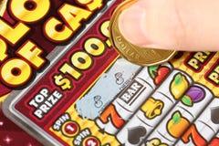 Ciérrese encima de la mujer que rasguña boletos de lotería Imagen de archivo libre de regalías