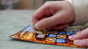Ciérrese encima de la mujer que rasguña el fuego llamado y el hielo del boleto de lotería dentro de la alameda de compras almacen de metraje de vídeo