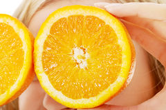 Ciérrese encima de la mujer que sostiene naranjas en ojos Imagen de archivo libre de regalías