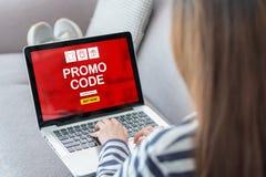 Ciérrese encima de la mujer trasera que hace compras en línea con código del promo en anuncio del ordenador portátil imagen de archivo libre de regalías