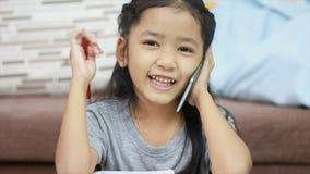 Ciérrese encima de la niña asiática del tiro que usa el lápiz que hace la preparación y hable con el smartphone metrajes