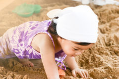 Ciérrese encima de la niña asiática que juega en la arena fotos de archivo libres de regalías