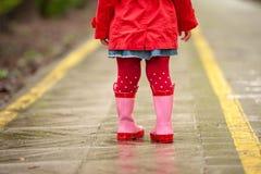 Ciérrese encima de la niña que camina al aire libre con rojo y botas color de rosa Foto de archivo