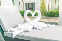 ciérrese encima de la opinión dos cisnes agradables de las toallas en cama Fotos de archivo libres de regalías