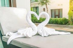 ciérrese encima de la opinión dos cisnes agradables de las toallas en cama Imagen de archivo
