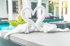 ciérrese encima de la opinión dos cisnes agradables de las toallas en cama Imágenes de archivo libres de regalías