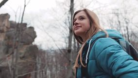 Ciérrese encima de la opinión el backpacker rubio atractivo que camina en el bosque del otoño, observando el paisaje Hojas que la almacen de video