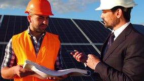 Ciérrese encima de la opinión el cliente del negocio que habla con el ingeniero en la estación de energía solar almacen de metraje de vídeo