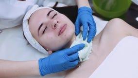 Ciérrese encima de la opinión el cosmetologist que saca los patient's hacen frente a la máscara atiesada de la belleza, las son metrajes
