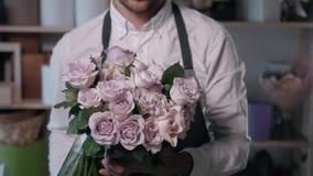 Ciérrese encima de la opinión el florista que prepara la composición de la flor en el lugar de trabajo, el ramo de peone de las r almacen de metraje de vídeo